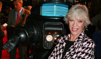 """** FILE ** Actress Anne Francis poses with Robby the Robot at a 2006 screening to commemorate the 50th anniversary of the science-fiction classic """"Forbidden Planet"""" in Los Angeles. Miss Francis, who was the love interest in that movie and later was sexy private eye Honey West on TV, has died at age 80. (AP Photo/Warner Home Video, Alan Berliner, File )"""