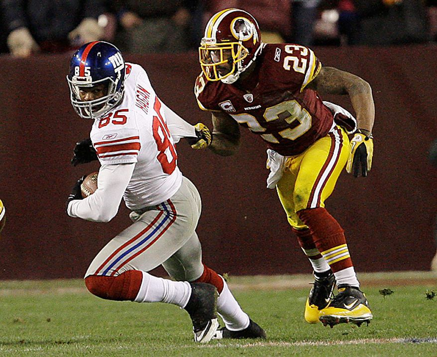 New York Giants wide receiver Derek Hagan (85) has his shirt pulled by Washington Redskins cornerback DeAngelo Hall (23) during the second half of an NFL football game in Landover, Md., on Sunday, Jan. 2, 2011. The Giants won, 17-14. (AP Photo/Jacquelyn Martin)