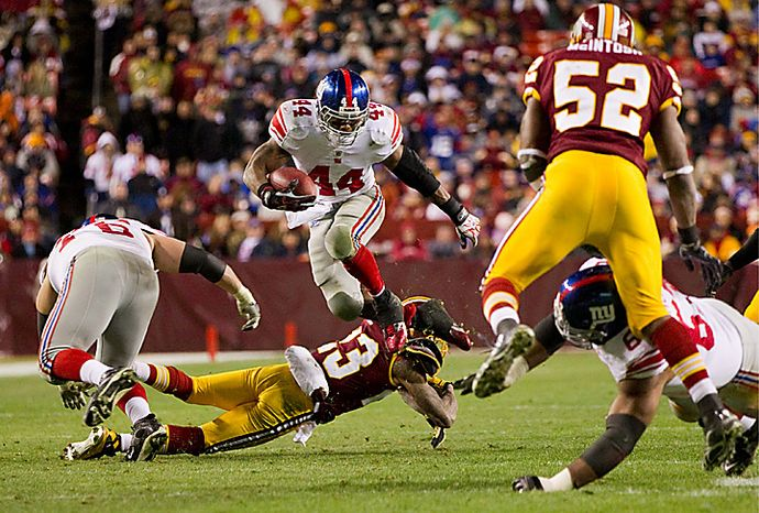 ** FILE ** New York Giants running back Ahmad Bradshaw (44) leaps over Washington Redskins cornerback DeAngelo Hall during the second half of an NFL football game on Sunday, Jan. 2, 2011, at FedEx Field in Landover, Md. The Giants defeated the Redskins, 17-14, but were eliminated from the playoffs with a Green Bay Packers victory over the Chicago Bears. From left are Giants guard Chris Snee, Bradshaw, Hall, Redskins linebacker Rocky McIntosh (52) and Giants offensive tackle Kareem McKenzie. (AP Photo/Evan Vucci)
