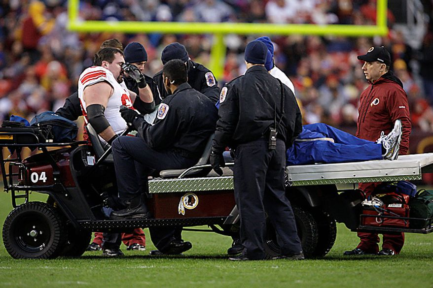 New York Giants center Rich Seubert is carted off the field with a dislocated right kneecap in the first quarter of an NFL football game against the Washington Redskins in Landover, Md., on Sunday, Jan. 2, 2011. (AP Photo/Jacquelyn Martin)