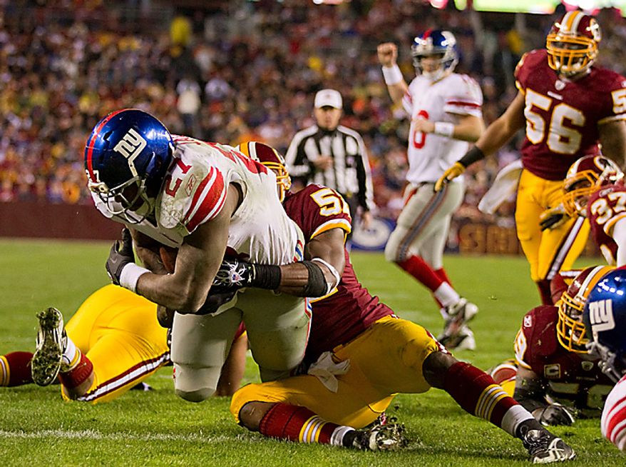 New York Giants running back Brandon Jacobs (27) drags Washington Redskins linebacker Rocky McIntosh (52) into the endzone for a touchdown during the first half of an NFL football game on Sunday, Jan. 2, 2011, in Landover, Md.  (AP Photo/Evan Vucci)