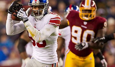 New York Giants wide receiver Michael Clayton (83) is chased by Washington Redskins defensive end Jeremy Jarmon (90) after making a reception during the first half of an NFL football game on Sunday, Jan. 2, 2011, in Landover, Md. (AP Photo/Evan Vucci)