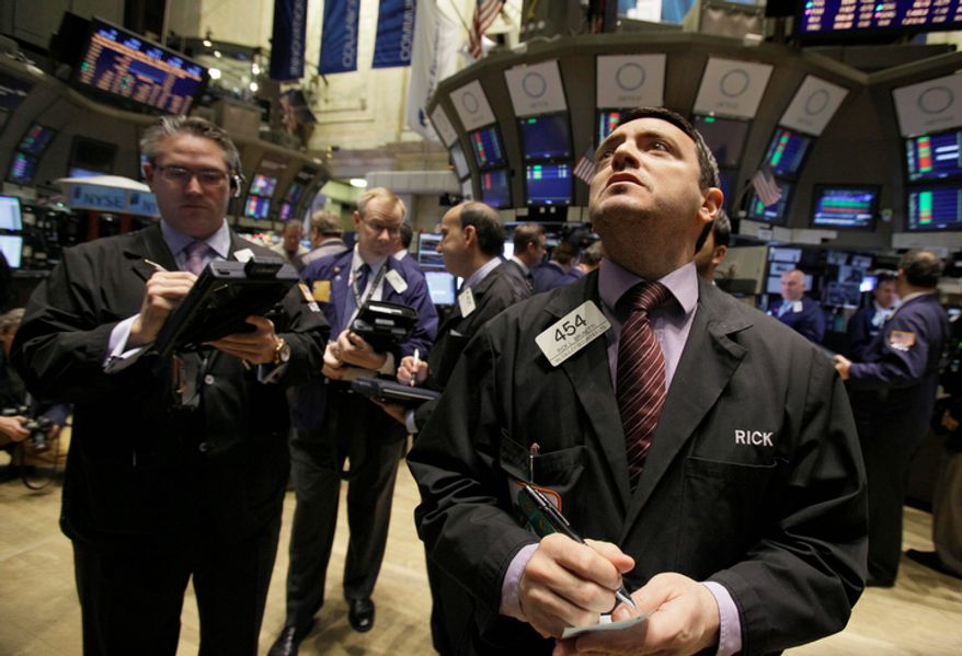 Trader Rick Brunetti (right) works on the floor of the New York Stock Exchange on Monday. The Dow Jones rose 93 points. (Associated Press)