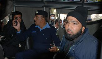 Commando of Pakistan's Elite force, Mumtaz Qadri, right, who purportedly killed Punjab's governor Salman Taseer, sits in a police custody in Islamabad, Pakistan on Tuesday, Jan. 4, 2011. (AP Photo/Irfan Ali)