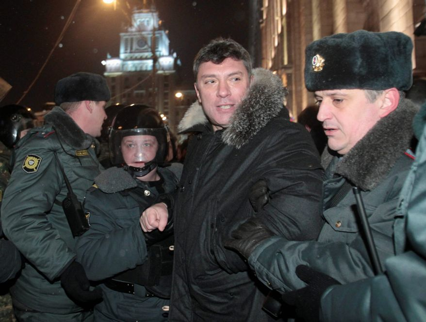 Riot police officers detain Russian opposition leader Boris Nemtsov during a rally in central Moscow on Friday. (Associated Press)