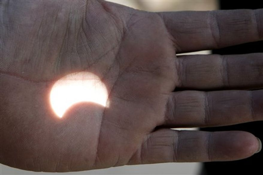 A Jordanian man uses his hand to show a reflected image of the partial solar eclipse, in Amman, Jordan, on Tuesday Jan. 4, 2011. A partial solar eclipse began Tuesday in the skies over the Mideast and extended across much of Europe. (AP Photo/Nader Daoud)