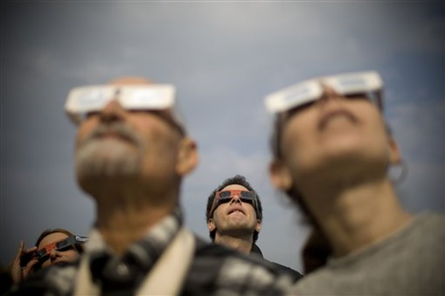 Israelis watch a partial solar eclipse in the town of Givatayim near Tel Aviv, Israel, Tuesday, Jan. 4, 2011. A partial solar eclipse began Tuesday in the skies over the Mideast and extended across much of Europe. (AP Photo/Ariel Schalit)