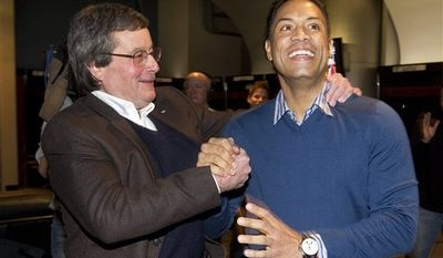 Toronto Blue Jays President and CEO Paul Beeston, left, congratulates former Blue Jays player Roberto Alomar in Toronto, Ont. as they watch the television announcement of Alomar's induction into the the Major League Baseball Hall of Fame Jan. 5, 2011. (AP Photo/The Canadian Press, Fred Thornhill,pool)