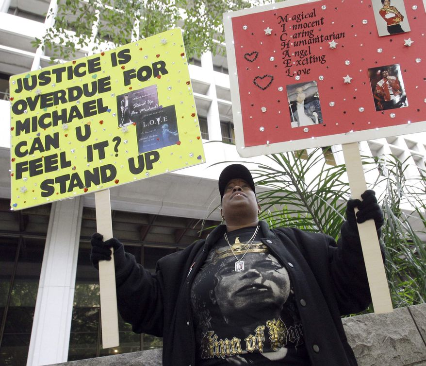 Michale Jackson fan Lesley Cole, of Los Angeles, poses with her signs as she shows her support for the late singer outside the preliminary hearing for Jackson's doctor Conrad Murray, charged in the death of the singer, at Los Angeles Superior Court, Wednesday, Jan. 5, 2011. (AP Photo/Reed Saxon)