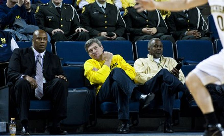 Michigan athletic director David Brandon, center, sits with assistant athletic directors Brian Townsend, left, and Greg Harden, right, at an NCAA college basketball game between Michigan and Penn State, Sunday, Jan. 2, 2011, in Ann Arbor, Mich. Brandon said a few hours after the Gator Bowl that he planned to meet with football coach Rich Rodriguez soon and expected to have something to announce later in the week. (AP Photo/Tony Ding)