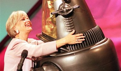 """FILE - In a March 7, 1998 file photo, actors Anne Francis and Robbie the Robot, who both starred in the 1956 science fiction thriller """"Forbidden Planet,"""" share a hug, during the taping of an Easter Seals television special in Los Angeles. Francis, who was the love interest in the 1950s science-fiction classic """"Forbidden Planet"""" and later was sexy private eye in """"Honey West"""" on TV, has died at age 80. Francis died Sunday, Jan 2, 2011 at a Santa Barbara nursing home, said Bill Guntle, a funeral director McDermott-Crockett & Associates Mortuary in Santa Barbara.  (AP Photo/John Hayes, File)"""