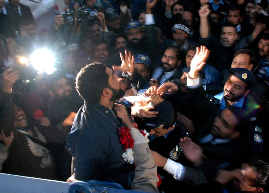 Mumtaz Qadri, foregroung, the suspected killer of Punjab's governor Salman Taseer, leaves a court in Islamabad, Pakistan on Wednesday, Jan. 5, 2011, mobbed by supporters. (AP Photo/Mohammad Riazur Rehman)