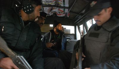 Mumtaz Qadri (center), a commando in Pakistan's Elite Force who is being held in the killing of Punjab Gov. Salman Taseer, sits in a police van in Islamabad, Pakistan, on Tuesday, Jan. 4, 2011. (AP Photo/Tariq Waseem)
