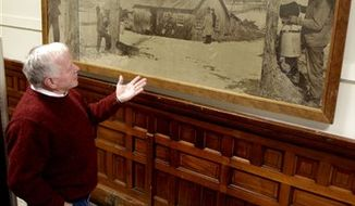 Vermont Agriculture Commissioner Roger Allbee stands by the newly-returned Norman Rockwell photo mural on Monday, Jan. 3, 2011 in Montpelier, Vt. The photographic mural of a maple sugar making scene by artist Norman Rockwell is hanging again in a hall of the Vermont Department of Agriculture. Rockwell created the black and white image of a sugar house with smoke coming from its chimney with people checking sap buckets after becoming friends with Henry Fairfax Ayers, once the chairman of the Vermont Sugar Makers Association.The mural, created in the late 1940s, was moved to the Rockwell Museum in Rutland in 1987 while the building was undergoing renovations.(AP Photo/Toby Talbot)