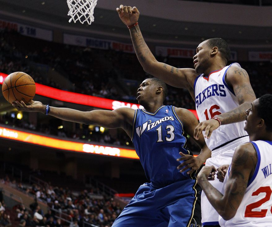 Washington Wizards' Kevin Seraphin (13) pulls in a rebound against Philadelphia 76ers' Marreese Speights (16) and Lou Williams (23) in the first half of an NBA basketball game, Wednesday, Jan. 5, 2011, in Philadelphia. (AP Photo/Matt Slocum)