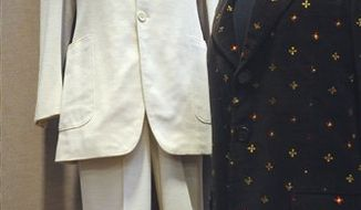 "FILE -- This Monday, Dec. 13, 2010 file photo shows two outfits worn by John Lennon at the Braswell Galleries in Norwalk, Conn. On the left is the suit Lennon wore in the photo on the cover of the The Beatles' Abbey Road album. On the right is a blazer he wore during his video for the song ""Imagine."" The white, two-piece suit sold at auction for $46,000 Saturday Jan. 2011.  (AP Photo/The Hour, Matthew Vinci/file) MANDATORY CREDIT"