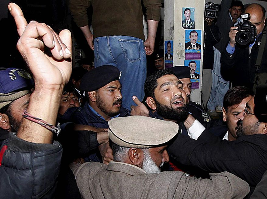 A Pakistani greets Mumtaz Qadri, third from right, the alleged killer of Punjab Gov. Salman Taseer, as he arrives at a court in Islamabad, Pakistan, on Wednesday, Jan. 5, 2011. Lawyers showered rose petals over the suspected killer of the prominent Pakistani governor when he arrived at court Wednesday, and an influential group of Muslim scholars praised the assassination of Mr. Taseer, an outspoken opponent of laws that order death for those who insult Islam. (AP Photo/B.K. Bangash)