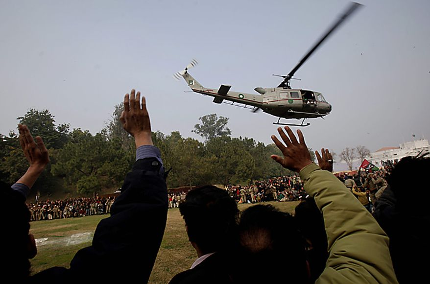 Pakistanis wave at a helicopter carrying the coffin of Punjab Gov. Salman Taseer as it departs for burial in Lahore, Pakistan, on Wednesday, Jan. 5, 2011. (AP Photo/Muhammed Muheisen)