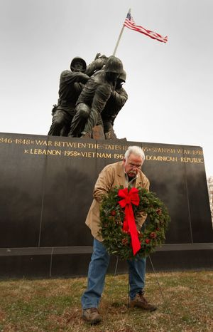 """James Donovan, founder and executive director of the Marine Corps War Memorial Foundation, places a wreath at the memorial during the Christmas wreath-laying ceremony on Dec. 13. """"As far as updates, we haven't kept pace with the times and its needs,"""" said Mr. Donovan, a former Marine corporal who served at the monument's Silent Drill Platoon from 1964 to 1968. (Sgt. Jimmy D. Shea/USMC)"""