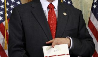 Rep. Darrell Issa, R-Calif., holds a copy of the U.S. Constitution during his mock swearing-in ceremony on Capitol Hill in Washington, Wednesday, Jan. 5, 2011. (AP Photo/Jacquelyn Martin)