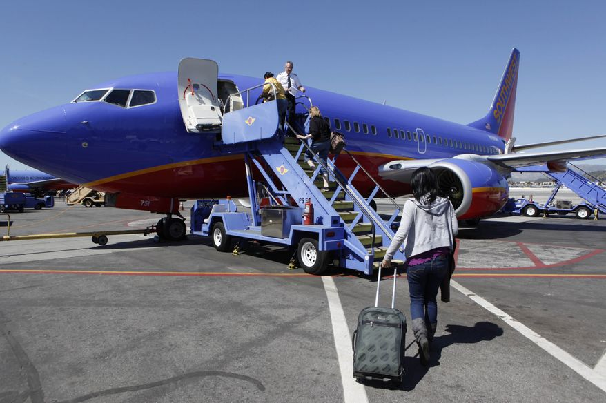 A March 13, 2010 photo shows people boarding a Southwest Airlines jet at Burbank, Calif., Airport. Southwest Airlines is revamping its frequent-flier program with changes designed to nudge customers into buying higher-priced tickets by letting them earn bonus flights faster. (AP Photo/Paul Sakuma)