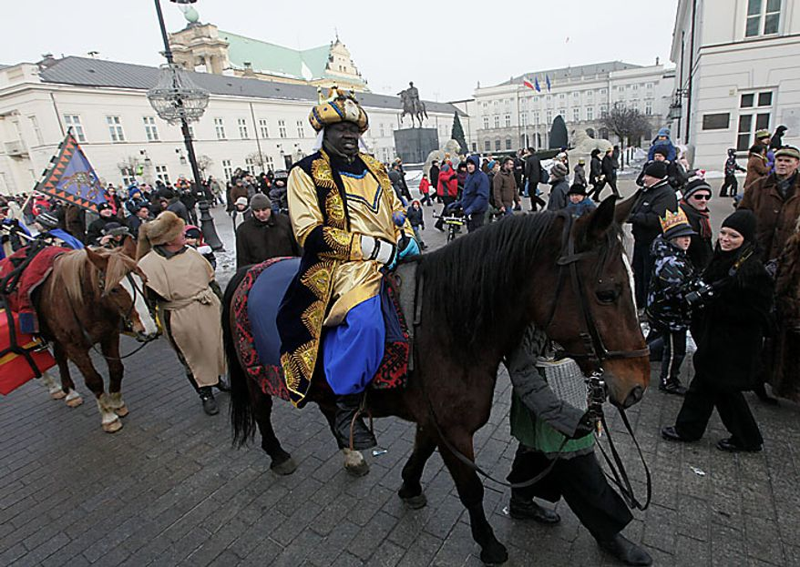 A volunteer dressed as one of the three kings carries gifts during the Epiphany parade through Warsaw on Thursday, Jan. 6, 2011. Poland observed Epiphany as an official public holiday for the first time in 50 years. The Epiphany feast day celebrates the visit of the three kings to the infant Jesus. (AP Photo/Czarek Sokolowski)