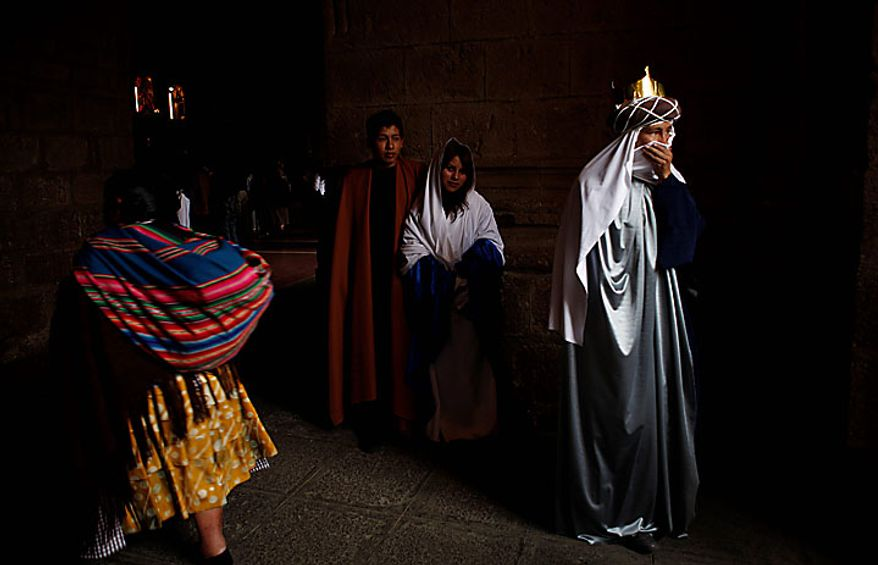 People dressed as one of the three kings (right) and Mary and Joseph (center) attend an Epiphany Mass at a Catholic church in La Paz, Bolivia, on Thursday Jan. 6, 2011. The feast day recalls the Gospel's account of the journey by the three kings, or wise men, guided by a star to pay homage to baby Jesus, and many faithful exchange gifts. (AP Photo/Juan Karita)
