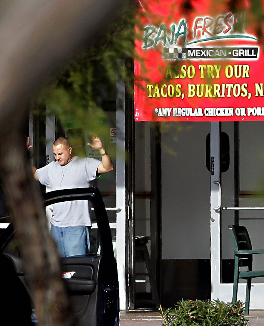 A man comes out of a Baja Fresh restaurant with his hands up Wednesday, Jan. 5, 2011 in Chandler, Ariz. Chandler police spokesman Sgt. Joe Favazzo says a gunman entered a Baja Fresh restaurant and fired a gun in what police think was a warning to customers following a shooting at the Chandler Mall. (AP Photo/Matt York)