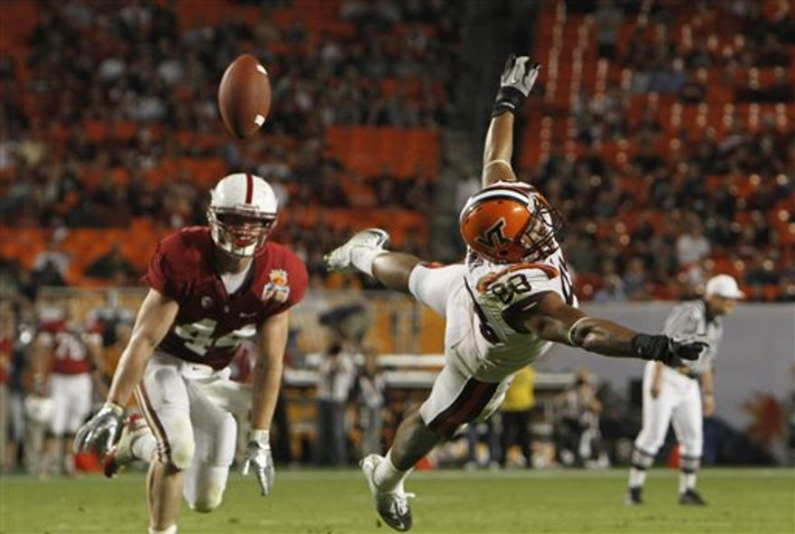 FILE- In this Jan. 3, 2011, file photo, Stanford linebacker Chase Thomas (44) watches as Virginia Tech's Andre Smith dives for a pass during the second half of the Orange Bowl NCAA college football game in Miami. Apathy appears to have set in among many college football fans toward the marquee games and bowl officials seem ready to explore ways to fix it. The problem isn't the national championship game. Ticket sales for other games have been sluggish and ratings generally have been lukewarm for matchups that haven't gotten the casual fan excited.(AP Photo/J Pat Carter, File)