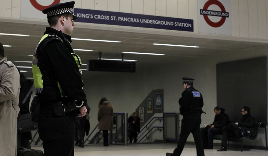Police officers patrol by an entrance to King's Cross underground train station in London, Friday, Jan. 7, 2011. More police officers were being deployed at transport hubs in London amid continuing fears of a terrorist attack, British media reported Thursday. (AP Photo/Matt Dunham)