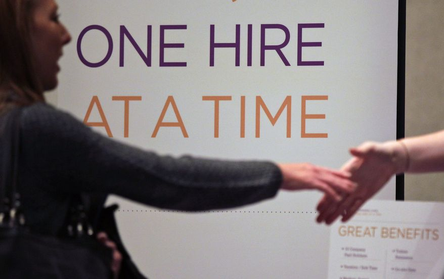 ** FILE ** In this file photo, Satila Higgins, of Evansville, Ind., speaks with a prospective employer at a career fair in San Diego. (AP Photo/Gregory Bull, File)