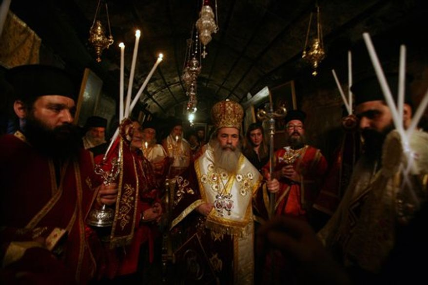 Greek Orthodox Patriarch of Jerusalem Theofilos III, center, walks surrounded by clergy during Orthodox Christmas services at the Church of Nativity, traditionally believed by many to be the birthplace of Jesus Christ, in the West Bank city of Bethlehem early Friday, Jan. 7, 2011. Christmas falls on Jan. 7 for Orthodox Christians in Eastern Orthodox churches that use the Julian calendar instead of the 16th-century Gregorian calendar adopted by Catholics and Protestants and commonly used in secular life around the world. (AP Photo/Nasser Shiyoukhi)