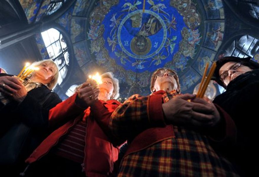 Women with candles in hands attend a holy Christmas liturgy in St. Clement's Cathedral in Macedonia's capital Skopje, Friday, Jan. 7, 2011. Macedonian Christian Orthodox believers celebrate Christmas by the Julian calendar. (AP Photo/Boris Grdanoski)