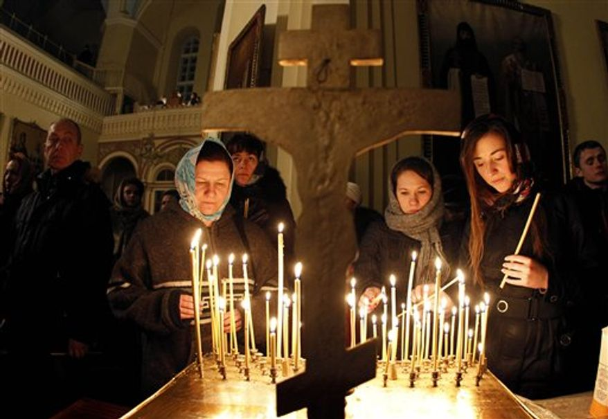 Lithuanian Orthodox Church believers light candles during the liturgy on Orthodox Christmas Eve in the Prechistensky the Cathedral Palace in Vilnius, Lithuania, Friday, Jan. 7, 2011. The Russian Orthodox Christians celebrate Christmas on Jan. 7, 2011, in accordance with the old Julian calendar. (AP Photo/Mindaugas Kulbis)