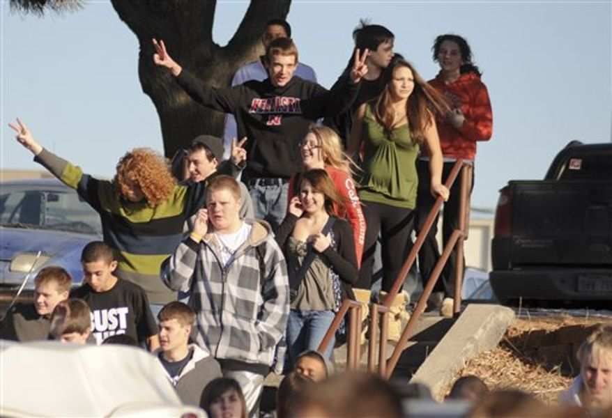 Millard South high school students give the V sign as they are let out of the school in Omaha, Neb., Wednesday, Jan. 5, 2011. Police say a 17-year-old who opened fire in the school fatally shot himself after leaving the school. (AP Photo/Dave Weaver)'