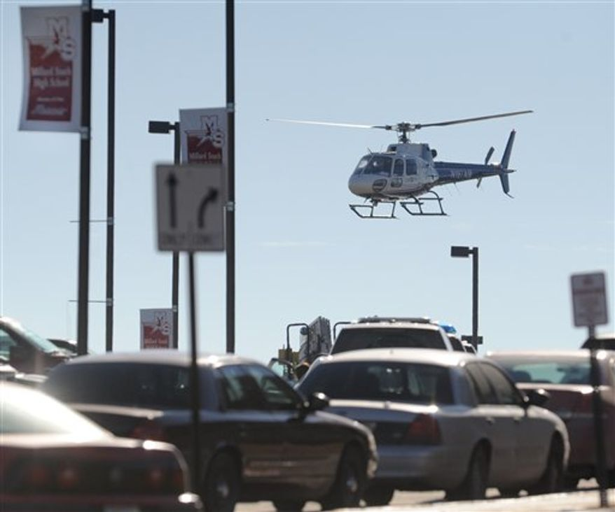 A medical helicopter lifts off from Millard South High School Wednesday, Jan 5, 2011, in Omaha, Neb.  A student shot and wounded two adults causing students to rush into a school kitchen to take cover before his body was found in a car about a mile away. (AP Photo/Dave Weaver)