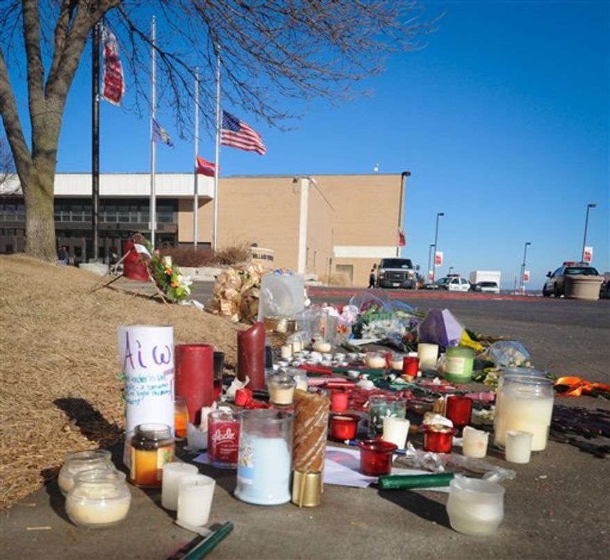 A memorial is arranged in front of Millard South High School, Thursday, Jan. 6, 2011, in Omaha, Neb., after a student shot and killed one administrator and wounded another. (AP Photo/Dave Weaver)