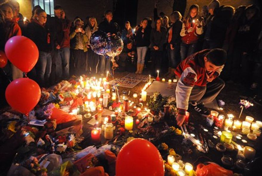 Millard South High School students hold a candle light vigil in front of the school Thursday Jan 6, 2011, in Omaha, Neb. A student opened fire killing the assistant principal, and wounding the principal on Wednesday. (AP Photo/Dave Weaver)