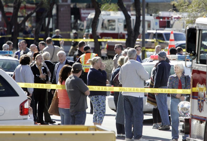 People gather at the scene of a shooting involving Rep. Gabrielle Giffords, D-Ariz., on Jan. 8, 2011, in Tucson, Ariz. (AP Photo/Arizona Daily Star, Dean Knuth)