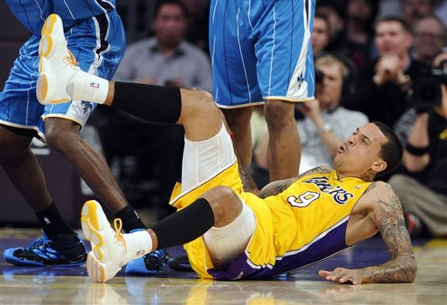 Los Angeles Lakers forward Matt Barnes, right, gets tied up with New Orleans Hornets guard Jarrett Jack as they go after a rebound during the first half of their NBA basketball game, Friday, Jan. 7, 2011, in Los Angeles. Barnes injured his knee on the play when he landed.  (AP Photo/Mark J. Terrill)