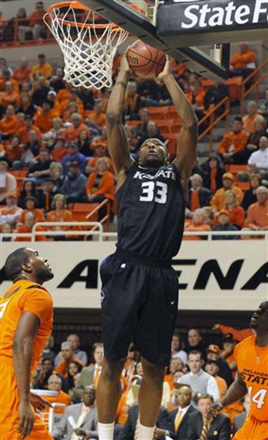 Oklahoma State forward Marshall Moses, left, and guard Ray Penn, right watch as Kansas State forward Wally Judge, center, takes a shot during the first half of an NCAA basketball game in Stillwater, Okla. Saturday, Jan. 8, 2011. (AP Photo/Brody Schmidt)