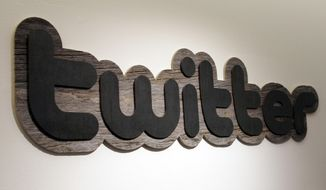 ** FILE ** A Twitter logo hangs at the offices of Twitter Inc. in San Francisco in 2010. (AP Photo/Jeff Chiu)