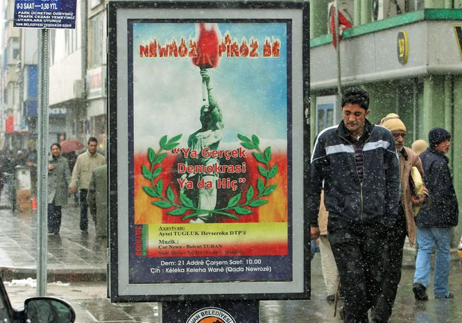 """Pedestrians in the eastern Turkish city of Van walk past a billboard celebrating the spring festival of Nowruz, with writing in Turkish and Kurdish reading """"Real democracy or nothing!"""" Since the latter part of 2010, Kurdish politicians and activists have aggressively promoted Kurdish in public settings, challenging its status as a restricted, once-shunned language, and alarming Turks who view the campaign as a threat to national unity and a harbinger of bolder demands for regional autonomy. (Associated Press)"""