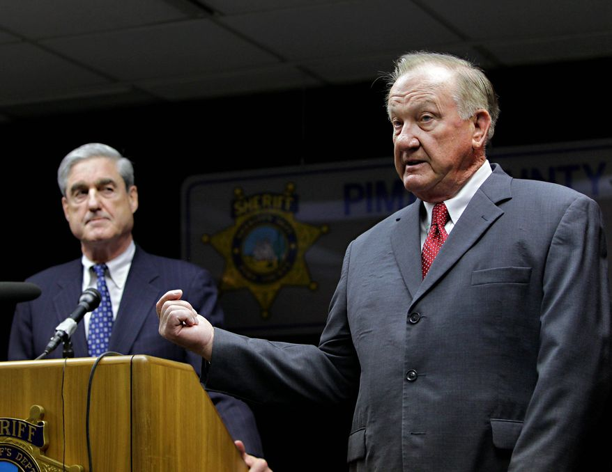FBI Director Robert S. Mueller III (left) listens as Pima County Sheriff Clarence Dupnik speaks on Sunday in Tucson, Ariz. Mr. Mueller was on hand to oversee the investigation of the shooting of Rep. Gabrielle Giffords, who was shot in the head a day earlier during a speech at a local supermarket. (Associated Press)