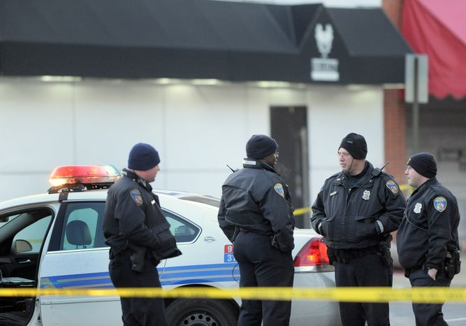 Police stand outside a Baltimore nightclub where an early-morning shooting left a police officer and another man dead on Sunday, Jan. 9, 2011. (AP Photo/Steve Ruark)