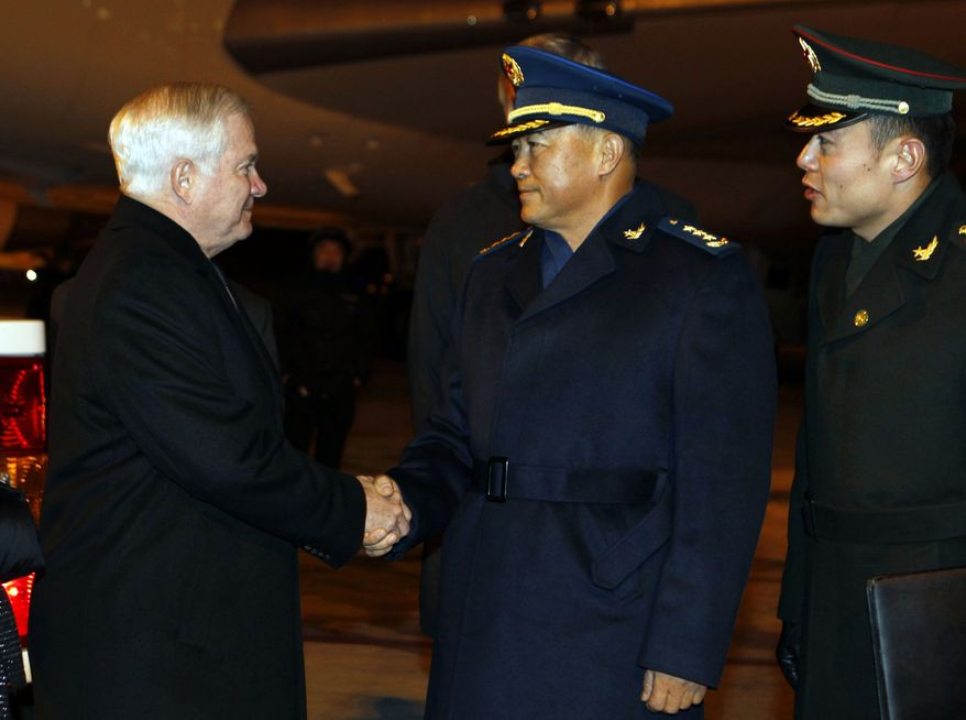 U.S. Secretary of Defense Robert M. Gates (left) is welcomed by Chief of the General's Staff Ma Xiaotian (center) upon arrival at Beijing International Airport in Beijing to start a four-day visit to China on Sunday, Jan. 9, 2011. (AP Photo/Larry Downing, Pool)