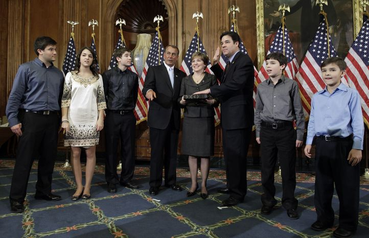House Speaker John A. Boehner (fourth from left), Ohio Republican, participates in the ceremonial swearing-in of Rep. Raul Labrador (third from right), Idaho Republican, on Capitol Hill in Washington on Wednesday, Jan. 5, 2011. Mr. Labrador's wife, Rebecca, and their five children also are pictured. (AP Photo/Charles Dharapak)