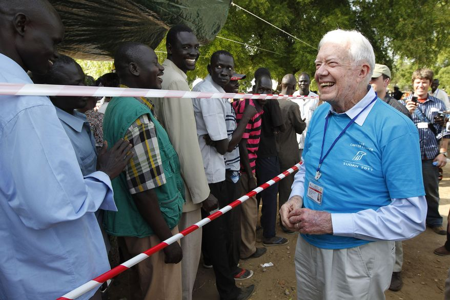 Former U.S. President Jimmy Carter (right) greets Southern Sudanese men waiting to cast their vote at a polling station in Juba, Southern Sudan, on Sunday, Jan 9, 2011. (AP Photo/Jerome Delay)