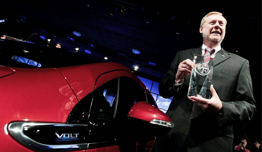 Tom Stephens, vice chairman of global product operations at General Motors Co., shows off the North American Car of the Year award won by the 2011 Chevrolet Volt electric car during the Detroit auto show. (Bloomberg)