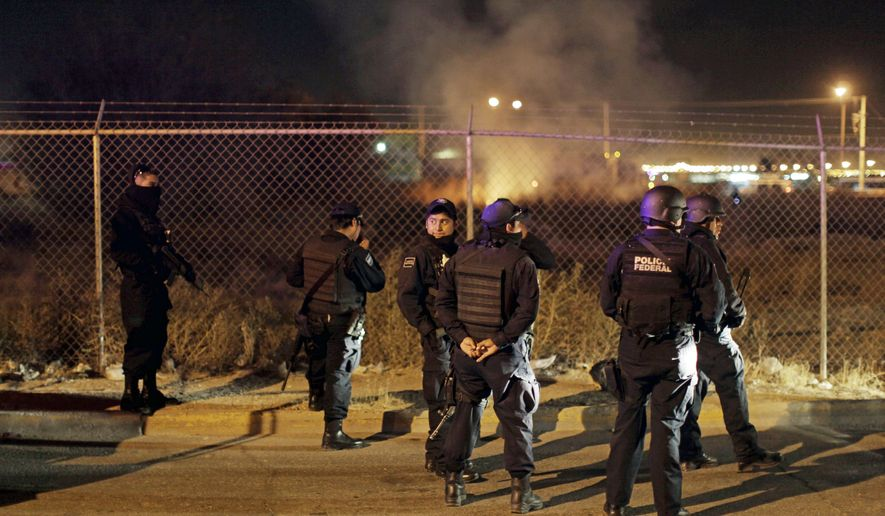 Mexican federal police cluster together Dec. 6 after a commando tried unsuccessfully to free inmates being transferred from the court back to prison in Ciudad Juarez. (Associated Press)